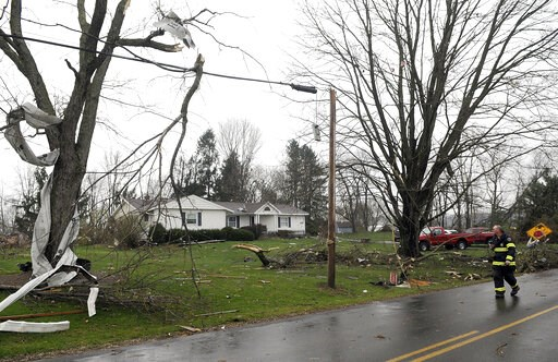 (Tom E. Puskar/The Times Gazette via AP). A Shelby firefighter walks down Plymouth Springmill Road just south of the intersection of Ohio Route 96, past damage to homes caused by severe weather, in Shelby, Ohio, Sunday, April 14, 2019.