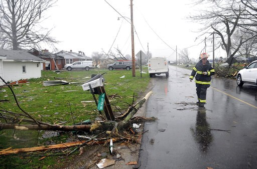 (Tom E. Puskar/The Times Gazette via AP). A Shelby firefighter walks down Plymouth Springmill Road just south of the intersection of Ohio Route 96, past severe storm damage to homes in Shelby, Ohio, Sunday, April 14, 2019.