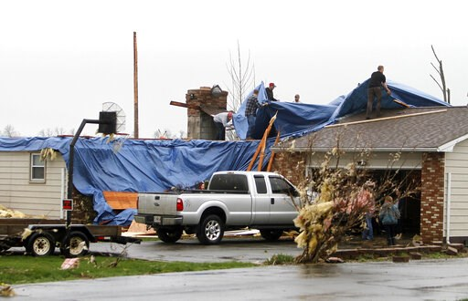 (Tom E. Puskar/The Times Gazette via AP). People work to cover the holes in a roof after severe weather damaged homes on Plymouth Springmill Road just south of the intersection of Ohio Route 96 in Shelby, Ohio, Sunday, April 14, 2019.