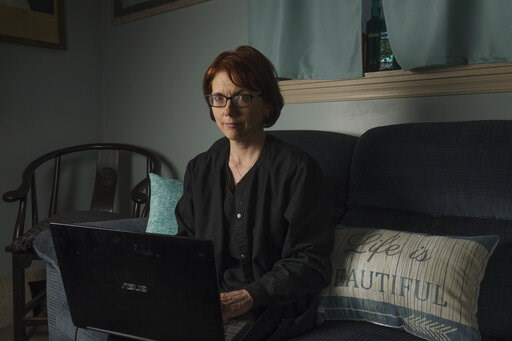 (AP Photo/Craig Hudson). In this Friday, April 5, 2019, photo, Kelly Povroznik poses for a portrait inside the living room of her home in Weston, W.Va. Povroznik teaches an online college course that has been hampered by slow connections on her compute...