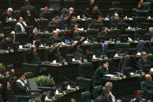 """(AP Photo/Hamidreza Rahel/ICANA). Wearing the uniform of the Iranian Revolutionary Guard, lawmakers chant slogan during an open session of parliament in Tehran, Iran, Tuesday, April 9, 2019. Chanting """"Death to America,"""" Iranian lawmakers convened an op..."""