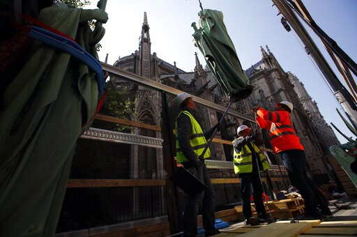 (AP Photo/Francois Mori). Workers secure a religious statue perched atop Paris' Notre Dame Cathedral as it descends to earth for the first time in over a century as part of a restoration, in Paris Thursday, April 11, 2019. The 16 greenish-gray copper s...