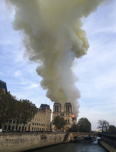 (AP Photo/Lori Hinant). Notre Dame cathedral is burning in Paris, Monday, April 15, 2019. Massive plumes of yellow brown smoke is filling the air above Notre Dame Cathedral and ash is falling on tourists and others around the island that marks the cent...