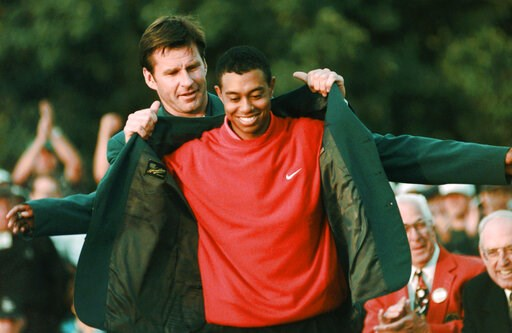 (AP Photo/Dave Martin, File). FILE - In this April 13, 1997, file photo, Masters champion Tiger Woods receives his Green Jacket from last year's winner Nick Faldo, rear, at the Augusta National Golf Club in Augusta, Ga. Woods completes an amazing journ...