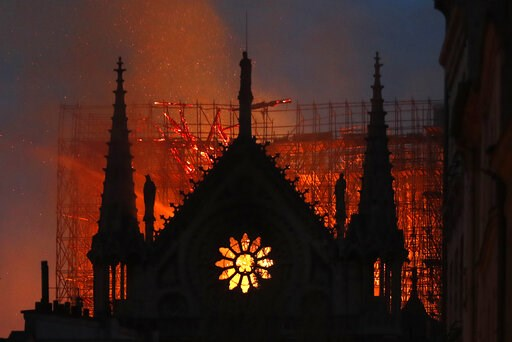 (AP Photo/Thibault Camus). Flames and smoke rise from Notre Dame cathedral as it burns in Paris, Monday, April 15, 2019. Massive plumes of yellow brown smoke is filling the air above Notre Dame Cathedral and ash is falling on tourists and others around...