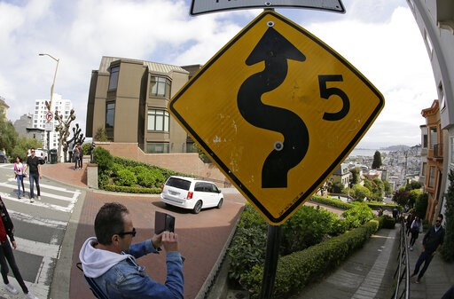 (AP Photo/Eric Risberg). A man takes pictures as cars wind their way down Lombard Street in San Francisco, Monday, April 15, 2019. Thousands of tourists may soon have to pay as much as $10 to drive down the world-famous curvy street if a proposal to es...
