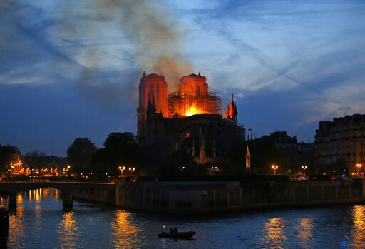(AP Photo/Michel Euler). Firefighters tackle the blaze as flames and smoke rise from Notre Dame cathedral as it burns in Paris, Monday, April 15, 2019. Massive plumes of yellow brown smoke is filling the air above Notre Dame Cathedral and ash is fallin...