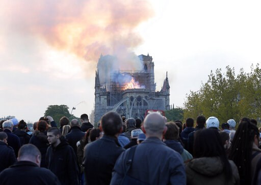 (AP Photo/Thibault Camus). People watch as flames and smoke rise from Notre Dame cathedral as it burns in Paris, Monday, April 15, 2019. Massive plumes of yellow brown smoke is filling the air above Notre Dame Cathedral and ash is falling on tourists a...