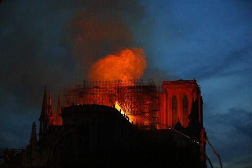 (AP Photo/Francois Mori). Firefighters use hoses as Notre Dame cathedral burns in Paris, Monday, April 15, 2019. A catastrophic fire engulfed the upper reaches of Paris' soaring Notre Dame Cathedral as it was undergoing renovations Monday, threatening ...