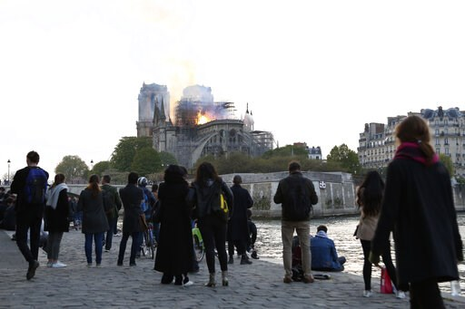 (AP Photo/Thibault Camus). People standing on the banks of the river Seine watch as flames and smoke rise from Notre Dame cathedral as it burns in Paris, Monday, April 15, 2019. Massive plumes of yellow brown smoke is filling the air above Notre Dame C...