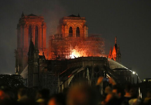 (AP Photo/Thibault Camus). Firefighters tackle the blaze as flames and smoke rise from Notre Dame cathedral as it burns in Paris, Monday, April 15, 2019. Massive plumes of yellow brown smoke is filling the air above Notre Dame Cathedral and ash is fall...