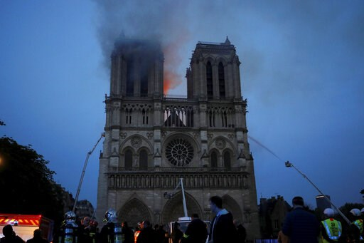 (Philippe Wojazer/Pool via AP). Smoke and flames fill the sky as a fire burns at the Notre Dame Cathedral during the visit by French President Emmanuel Macron in Paris, Monday, April 15, 2019. A catastrophic fire engulfed the upper reaches of Paris' so...