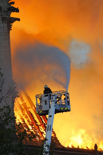 (AP Photo/Francois Mori). A fire fighter uses a hose as Notre Dame cathedral is burning in Paris, Monday, April 15, 2019. A catastrophic fire engulfed the upper reaches of Paris' soaring Notre Dame Cathedral as it was undergoing renovations Monday, thr...