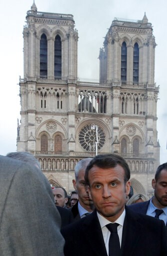 (Philippe Wojazer/Pool via AP). French President Emmanuel Macron walks by Notre Dame Cathedral during his visit to the site in Paris, Monday, April 15, 2019. A catastrophic fire engulfed the upper reaches of Paris' soaring Notre Dame Cathedral as it wa...