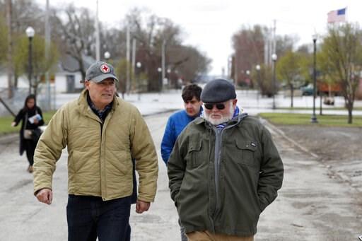 (AP Photo/Charlie Neibergall). 2020 Democratic presidential candidate Washington Gov. Jay Inslee, left, walks with climate analyst John Davis, of Hamburg, Iowa, while touring flood damage, Friday, April 12, 2019, in Hamburg, Iowa.