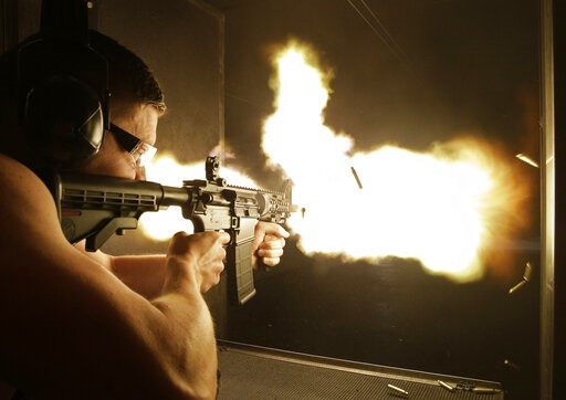 (AP Photo/John Locher, File). FILE - In this Thursday, Aug. 28, 2014, file photo, Simon Winson of Manchester, England fires a fully automatic machine gun at Machine Guns Vegas in Las Vegas. Strict gun laws keep the real guns out of reach for most peopl...