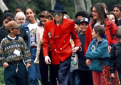 (AP Photo/Mark J. Terrill, File). FILE - In this April 18, 1995, file photo, pop star Michael Jackson and Lisa Marie Presley, behind him at left, walk with children that were invited guests at his Neverland Ranch home in Santa Ynez, Calif. The co-execu...