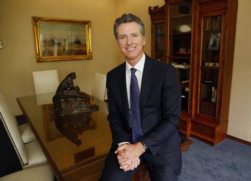 (AP Photo/Rich Pedroncelli). In this photo taken Monday April 15, 2019 Gov. Gavin Newsom poses for a photo at his Capitol office in Sacramento, Calif. In Newsom's first 100 days as governor, he's traveled to Central America, battled with the Trump admi...