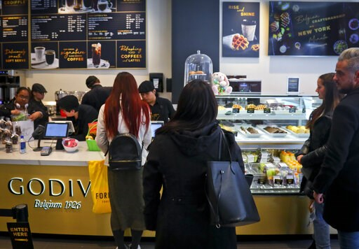 (AP Photo/Bebeto Matthews). Customers wait in line for service at Godiva's new cafe in New York, Tuesday April 16, 2019. Godiva, the private Belgium chocolate maker, is looking beyond its iconic gold gift box of chocolates. The confectioner is rolling ...