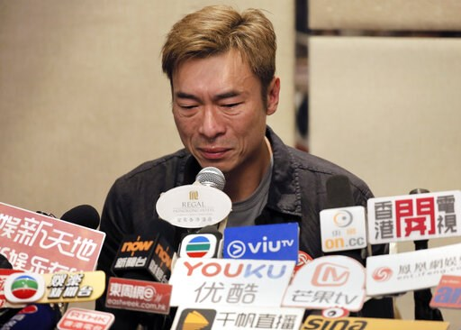 (AP Photo/Vincent Yu). Hong Kong singer Andy Hui reacts during a press conference about his affair in Hong Kong, Tuesday, April 16, 2019. Hong Kong's Apple Daily newspaper published video that purported to show Andy Hui being intimate in a taxi with an...