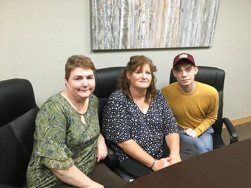 (AP Photo/Blake Nicholson). In this Sunday, April 14, 2019, photo, RJR Maintenance and Management office manager Deanna Finnie, left, co-owner Jackie Fakler, center, and marketing executive Ben Pace pose for a photograph at the business in Mandan, N.D....