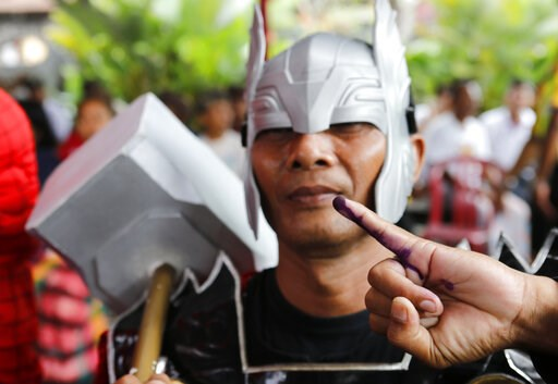 (AP Photo/Firdia Lisnawati). A man in Thor's costume shows his inked finger after casting at a polling station during election in Bali, Indonesia on Wednesday, April 17, 2019. Voting is underway in Indonesia's presidential and legislative elections aft...