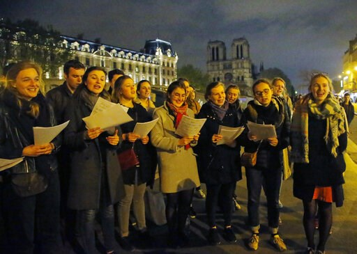 (AP Photo/Michel Euler). People attend a vigil in Paris, Tuesday April 16, 2019. Firefighters declared success Tuesday in a more than 12-hour battle to extinguish an inferno engulfing Paris' iconic Notre Dame cathedral that claimed its spire and roof, ...