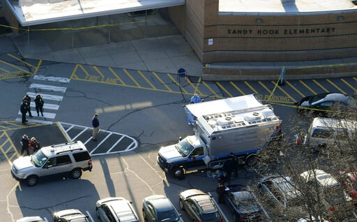 (AP Photo/Julio Cortez, File). FILE - In this Dec. 14, 2012, aerial file photo, officials stand outside of Sandy Hook Elementary School in Newtown, Conn., where gunman Adam Lanza opened fire inside school killing 20 first-graders and six educators at t...