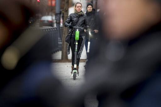 (AP Photo/Andrew Harnik). In this Dec. 4, 2018, photo a couple rides scooters near the White House in Washington. Electric scooters are overtaking station-based bicycles as the most popular form of shared transportation outside transit and cars.