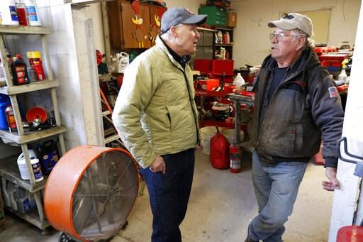 (AP Photo/Charlie Neibergall). 2020 Democratic presidential candidate Washington Gov. Jay Inslee talks with Ron Perry, of Hamburg, Iowa, right, while touring flood damage, Friday, April 12, 2019, in Hamburg, Iowa.