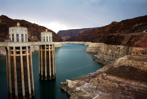 (AP Photo/John Locher, File). FILE - In this July 28, 2014, file photo, lightning strikes over Lake Mead near Hoover Dam that impounds Colorado River water at the Lake Mead National Recreation Area in Arizona. President Donald Trump on Tuesday, April 1...