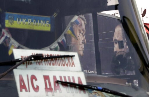 (AP Photo/Sergei Grits). A bus drives past a billboard depicting Ukraine's President Petro Poroshenko and Russian President Vladimir Putin looking at each other in Kiev, Ukraine, Wednesday, April 17, 2019. The second round of presidential vote in Ukrai...
