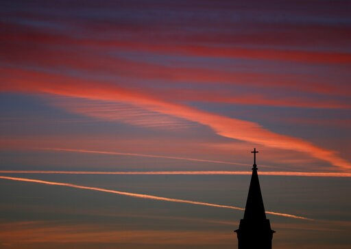 (AP Photo/Charlie Riedel). FILE - In this Saturday, Jan. 18, 2014 file photo, contrails from jets glow pink as they are illuminated by the setting sun in the skies beyond a church in Kansas. According to a Gallup poll released on Thursday, April 18, 20...
