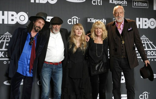 (Photo by Charles Sykes/Invision/AP, File). FILE - This March 29, 2019 file photo shows Inductee Stevie Nicks, center, posing with other members of Fleetwood Mac, from left, Mike Campbell, John McVie, Christine McVie and Mick Fleetwood at the Rock &amp...