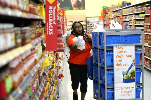 (AP Photo/David J. Phillip, File). FILE - In this Nov. 9, 2018, file photo, Walmart associate Alicia Carter fulfills online grocery orders at a Walmart Supercenter in Houston. Amazon and Walmart on Thursday, April 18, 2019, are kicking off a two-year p...