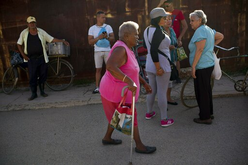 (AP Photo/Ramon Espinosa). Pura Castell walks to a government-run butcher shop to buy chicken, after failing to find chicken the previous day in Bauta, Cuba, Friday, April 12, 2019. A neighbor informed her that chicken had arrived at the government sto...
