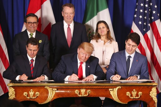 (AP Photo/Martin Mejia, File). FILE - In this Nov. 30, 2018 file photo, President Donald Trump, center, sits between Canada's Prime Minister Justin Trudeau, right, and Mexico's President Enrique Pena Nieto as they sign a new United States-Mexico-Canada...