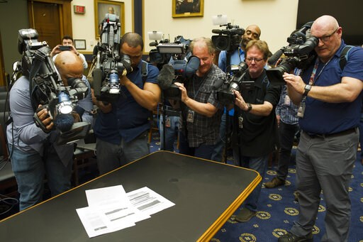 (AP Photo/Cliff Owen). Photojournalists photograph four pages of the Mueller Report laid on the witness table in the House Intelligence Committee hearing room on Capitol Hill, in Washington, Thursday, April 18, 2019.