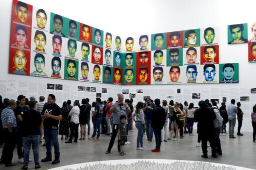 (AP Photo/Claudio Cruz). People stand under the portraits of 43 college students who went missing in 2014 in an apparent massacre, by Chinese concept artist and government critic Ai Weiwei at the Contemporary Art University Museum (MUAC ) in Mexico Cit...