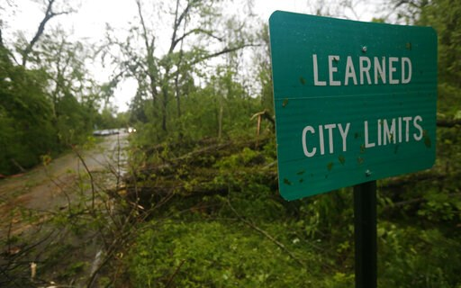 (AP Photo/Rogelio V. Solis). Fallen trees line the roads leading into the small community of Learned, Miss., Thursday, April 18, 2019. Several homes were damaged by fallen trees in the tree lined community. Strong storms again roared across the South o...