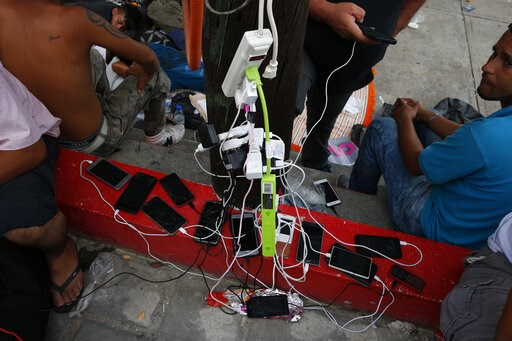 (AP Photo/Rebecca Blackwell, File). FILE - In this Oct. 28, 2018 file photo, migrants charge their cell phones as a caravan of Central Americans trying to reach the U.S. border halts for a rest day in San Pedro Tapanatepec, Oaxaca state, Mexico. Hundre...