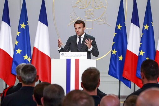 (Christophe Petit Tesson, Pool via AP). French President Emmanuel Macron addresses Paris Firefighters' brigade and security forces who took part at the fire extinguishing operations of the Notre Dame of Paris Cathedral fire, at the Elysee Palace in Par...
