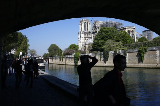 (AP Photo/Thibault Camus). Tourists walk nearby Notre Dame cathedral, in Paris, Friday, April 19, 2019. Rebuilding Notre Dame, the 800-year-old Paris cathedral devastated by fire this week, will cost billions of dollars as architects, historians and ar...