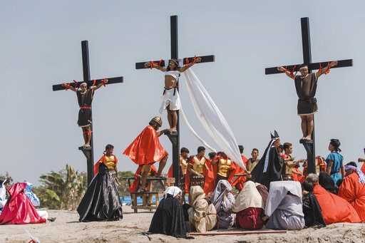 (AP Photo/Iya Forbes). Ruben Enaje, center, dressed as Jesus, is seen nailed on cross for the 33rd year in a row during a reenactment of Jesus Christ's sufferings as part of Good Friday rituals in the village of San Pedro Cutud, Pampanga province, nort...