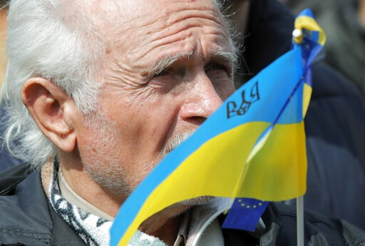 (AP Photo/Vadim Ghirda). A man holds an Ukrainian flag as protesters gather to march to the Olympic stadium ahead of debates between two candidates in the weekend presidential run-off in Kiev, Ukraine, Friday, April 19, 2019. Friday is the last officia...