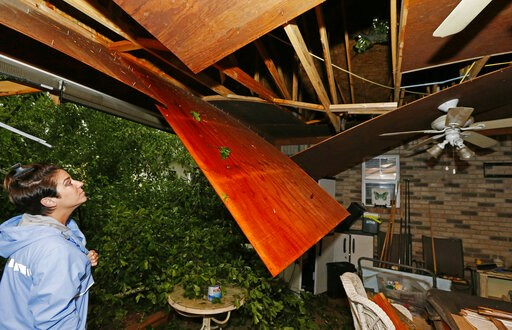 (AP Photo/Rogelio V. Solis). Sonya Banes looks at damage caused by a large oak tree that crashed through the ceiling of her mother's house in Learned, Miss., Thursday, April 18, 2019. Several homes were damaged by fallen trees in the tree lined communi...