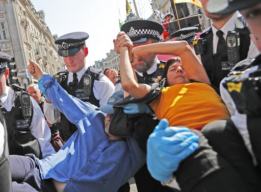 (AP Photo/Frank Augstein). Police arrest a protestor couple who are glued together by their hands, at Oxford Circus in London, Friday, April 19, 2019. The group Extinction Rebellion is calling for a week of civil disobedience against what it says is th...