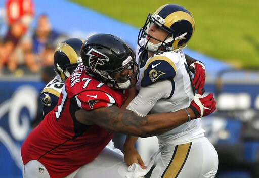 (AP Photo/Mark J. Terrill, File). FILE - In this Dec. 11, 2016, file photo, Los Angeles Rams quarterback Jared Goff, right, is hit by Atlanta Falcons defensive tackle Ra'Shede Hageman during the second half of an NFL football game in Los Angeles. The F...