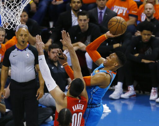 (AP Photo/Sue Ogrocki). Oklahoma City Thunder guard Russell Westbrook, right, shoots in front of Portland Trail Blazers center Enes Kanter (00) I the first half of Game 3 of an NBA basketball first-round playoff series Friday, April 19, 2019, in Oklaho...