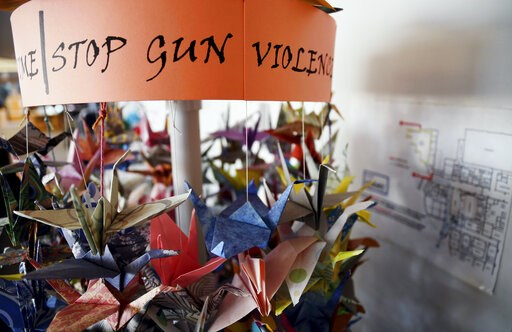 (AP Photo/Thomas Peipert, File). FILE - In this March 23, 2019, file photo, origami cranes, a symbol of peace, hang in the Columbine High School library in Littleton, Colo., near where several survivors and family members of the victims gathered to spe...
